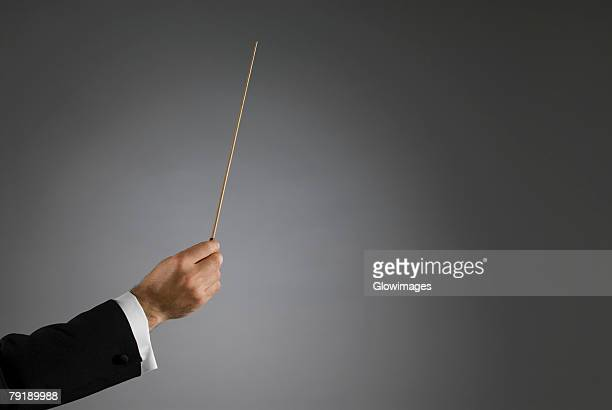 Close-up of a conductor's hand holding a conductor's baton
