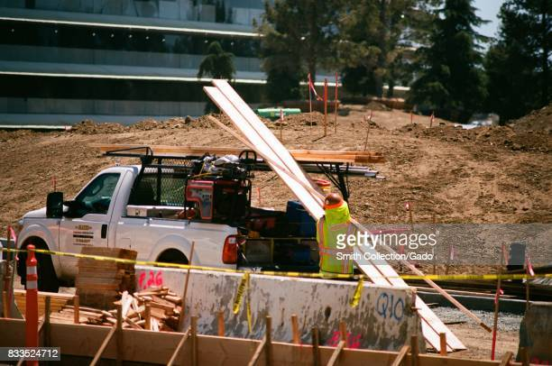Closeup of a construction worker with a high visibility vest loading construction materials onto a pickup truck with portion of the main building...
