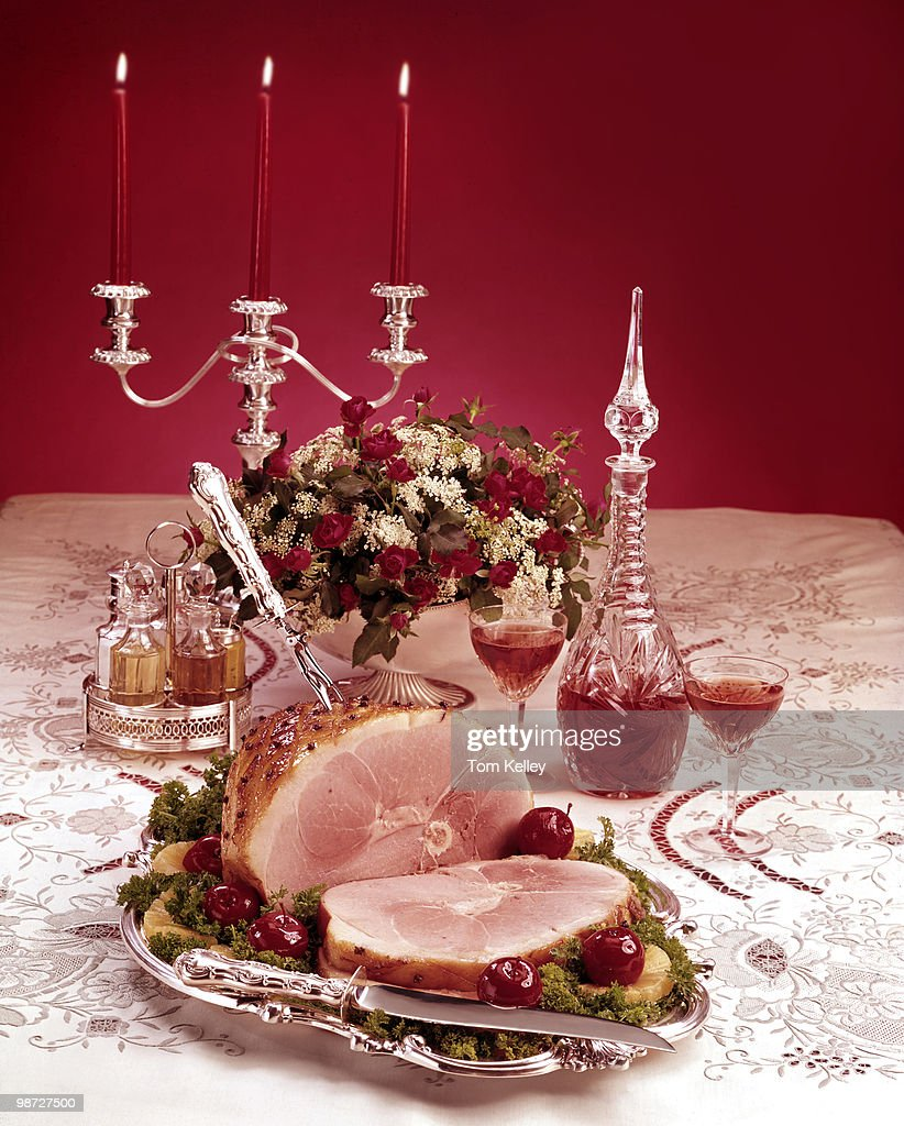 Closeup of a cooked ham on a serving plate next to a candelabra and wine decanter 1978