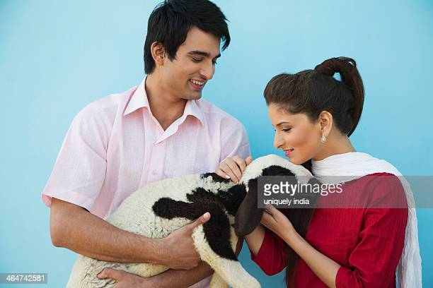 Close-up of a couple carrying a lamb