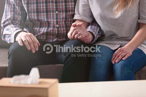 Close-up of a couple holding hands together while sitting on a couch during a therapy : Stock Photo