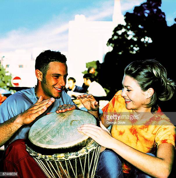 close-up of a couple sitting and beating on a drum; smiling