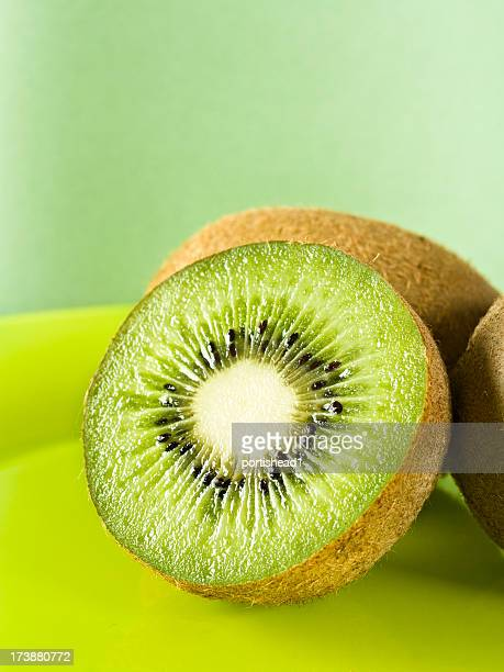 Close-up of a cut kiwi on a green plate