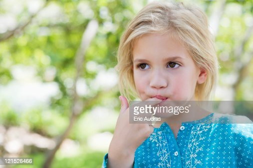 Close-up of a cute girl eating something outdoors : Stock Photo