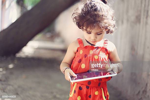 Close-up of a cute little girl using a digital tablet