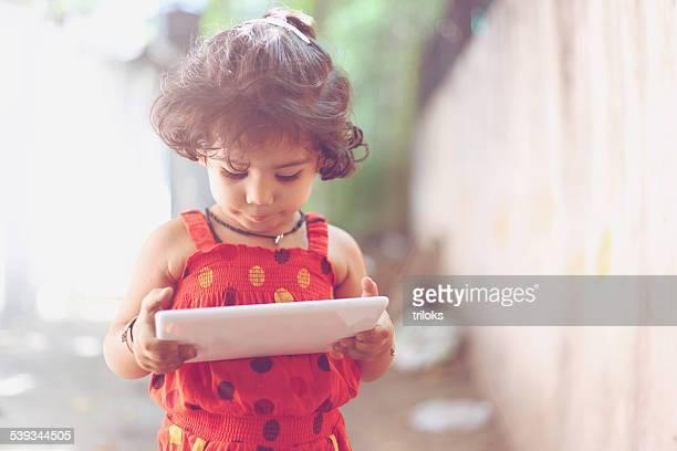 Close-up de um bonito menina usando um tablet digital