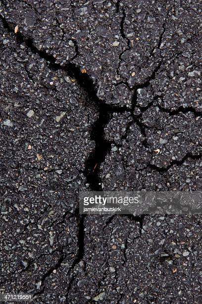 Close-up of a dark gray cracked asphalt pavement
