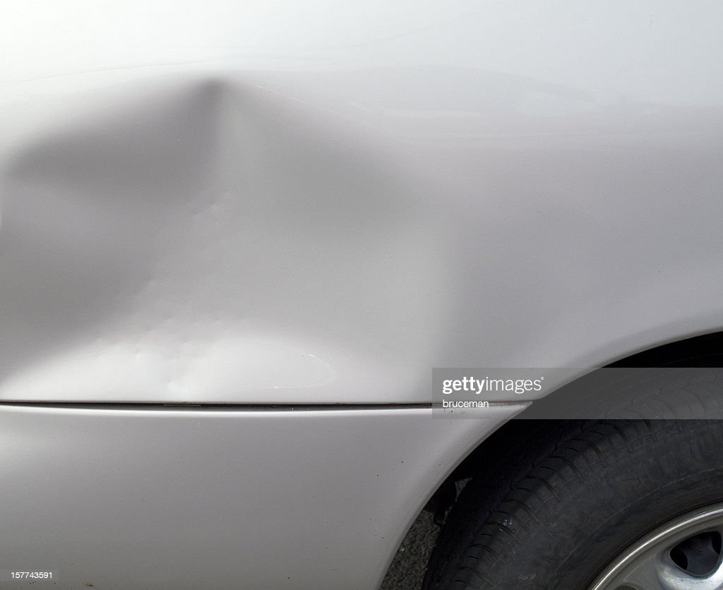 Close-up of a dent in a gray car exterior