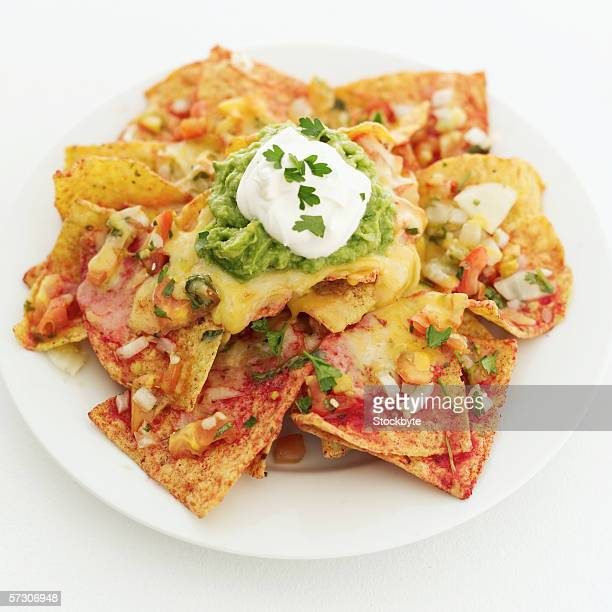 Close-up of a dish of nachos dressed with cheese