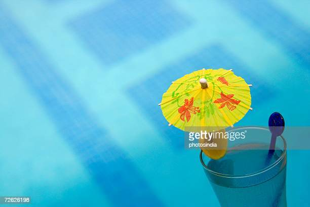 Close-up of a drink umbrella in a glass of juice