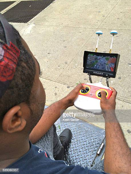CloseUp of a Drone Pilot Using the Remote Control System to Fly a Drone While Sitting on a Sidewalk in Fort Greene Brooklyn NYC the Streetscape and...