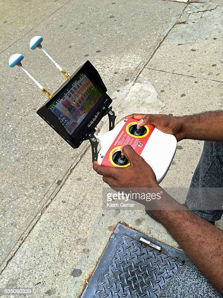 CloseUp of a Drone Pilot's Hands on the Remote Control System as He Flies a Drone While Sitting on a Sidewalk in Fort Greene Brooklyn NYC the Flight...