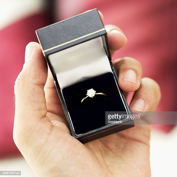 close-up of a engagement ring in a man's hand