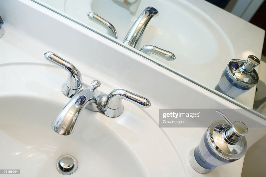 Close-up of a faucet and a soap dispenser on a bathroom sink : Stock Photo