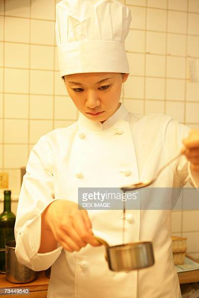 Close-up of a female chef checking sauce in a pan with a spoon