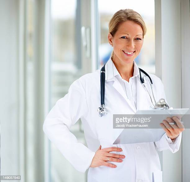 Close-up of a female doctor holding clipboard and smiling