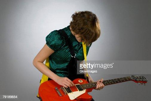 Close-up of a female guitarist playing a guitar : Foto de stock