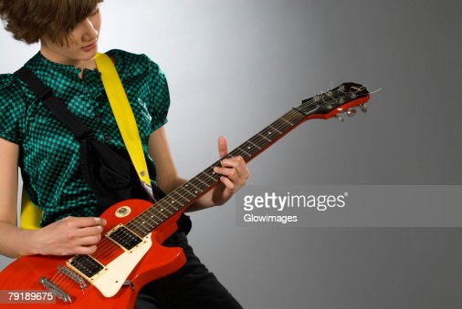 Close-up of a female guitarist playing a guitar : Stock Photo