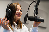 Close-up of a Happy young female jockey communicating on microphone in radio studio