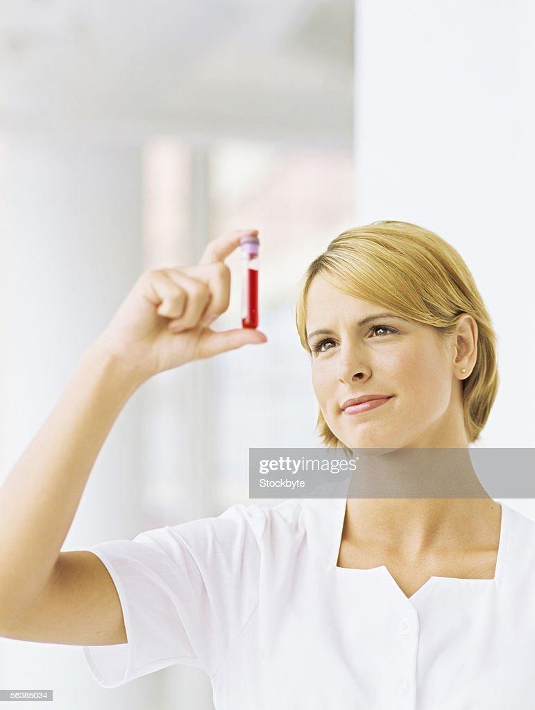 close-up of a female nurse holding a test tube : Stock Photo