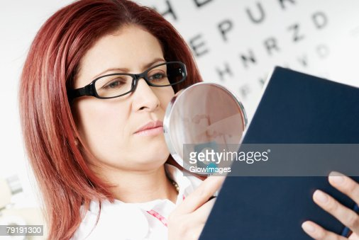 Close-up of a female optometrist examining a report with a magnifying glass : Foto de stock