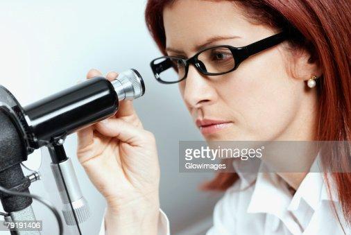 Close-up of a female optometrist using a phoropter : Foto de stock