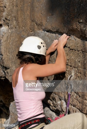 Close-up of a female rock climber scaling a rock face : Foto de stock
