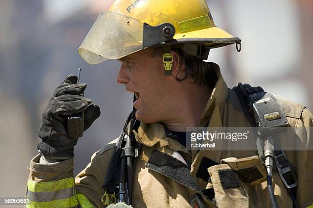 Close-up of a firefighter holding a walkie-talkie