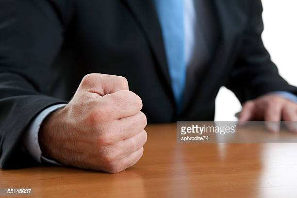 Close-up of a fist of a furious businessman on a table
