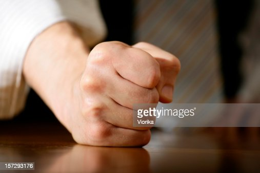Close-up of a fist resting on a wooden surface