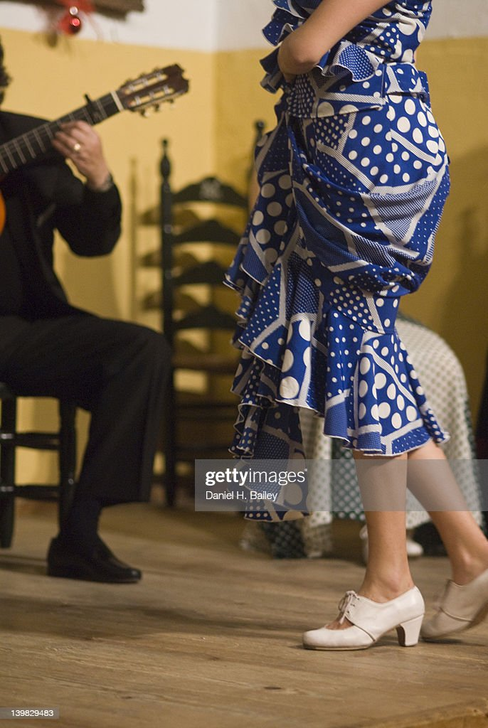 Close-up of a flamenco dancer's legs, feet and traditional dress and guitar players performing on stage, Jerez de la Frontera, Andalucia, Southern Spain : Stock Photo