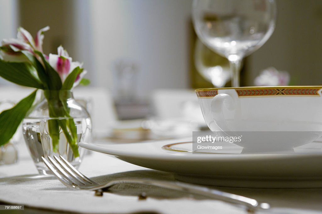 Close-up of a flower vase and a soup bowl on a dining table : Stock Photo