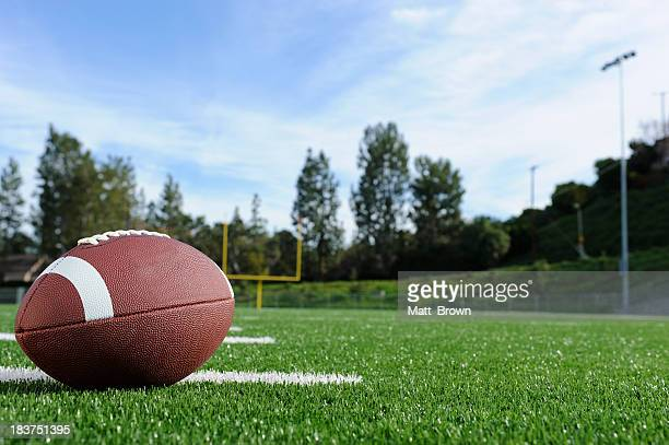 Close-up of a football on a field with view of the goalpost