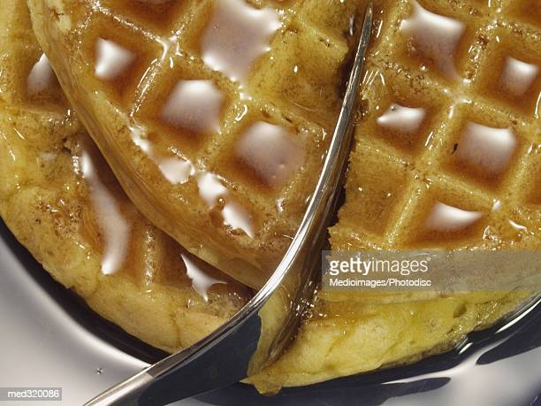 Close-up of a fork cutting into pancakes with maple syrup