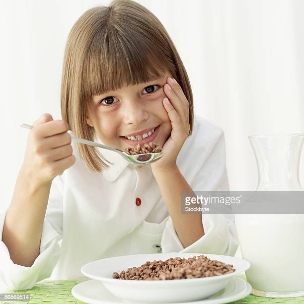 close-up of a girl eating chocolate cereal