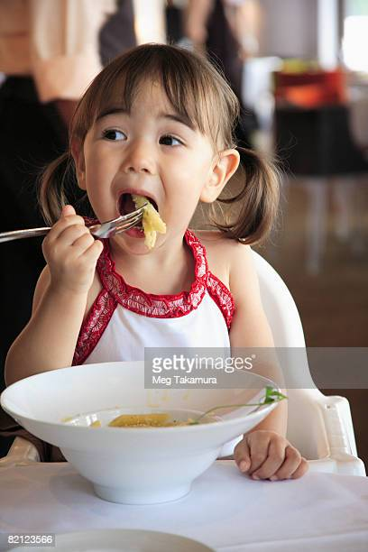 Close-up of a girl eating fruit with a fork