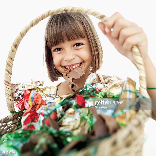 Close-up of a girl (6-8) holding a basketful of candy