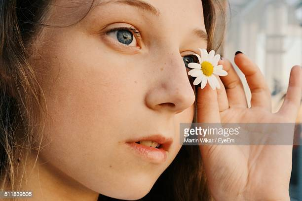 Close-up of a girl holding a daisy flower near her eye
