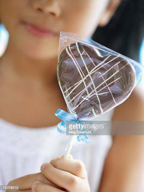 Close-up of a girl holding a heart shaped lollipop