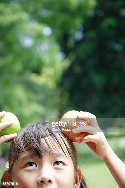 Close-up of a girl holding apples on her head