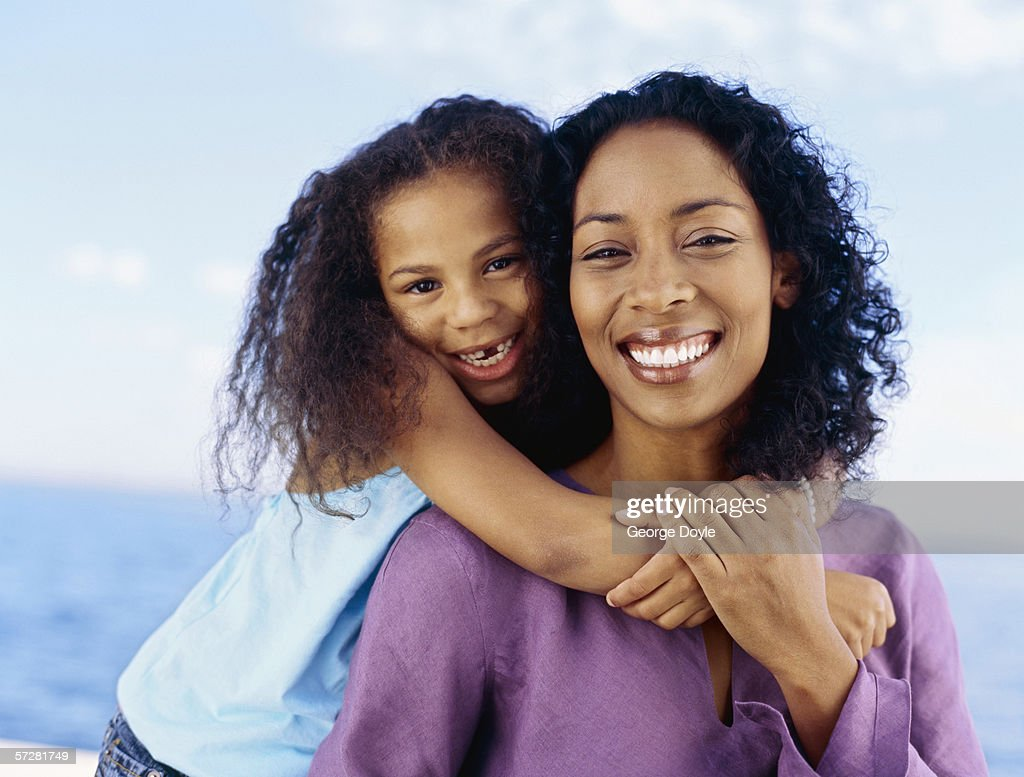 Close-up of a girl hugging her mother