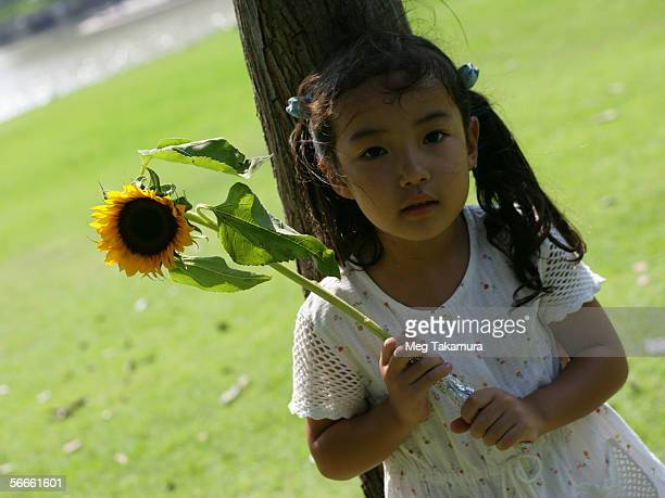 Close-up of a girl leaning against a tree and holding a sunflower