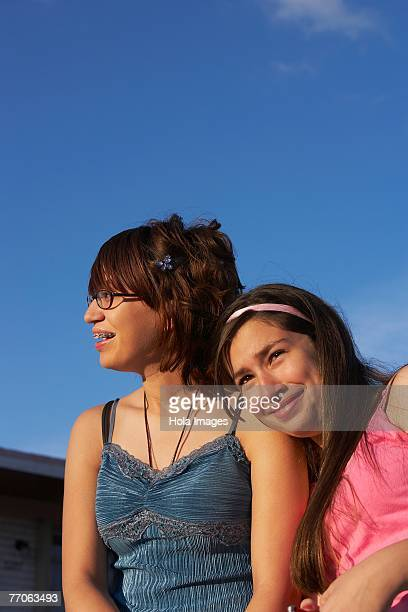 Close-up of a girl leaning on a teenage girl's shoulder