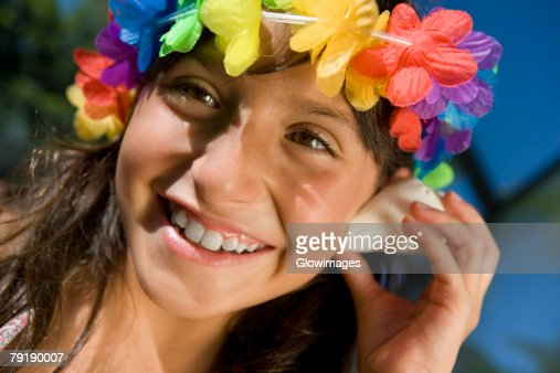 Close-up of a girl listening to a conch shell and smiling : Foto de stock