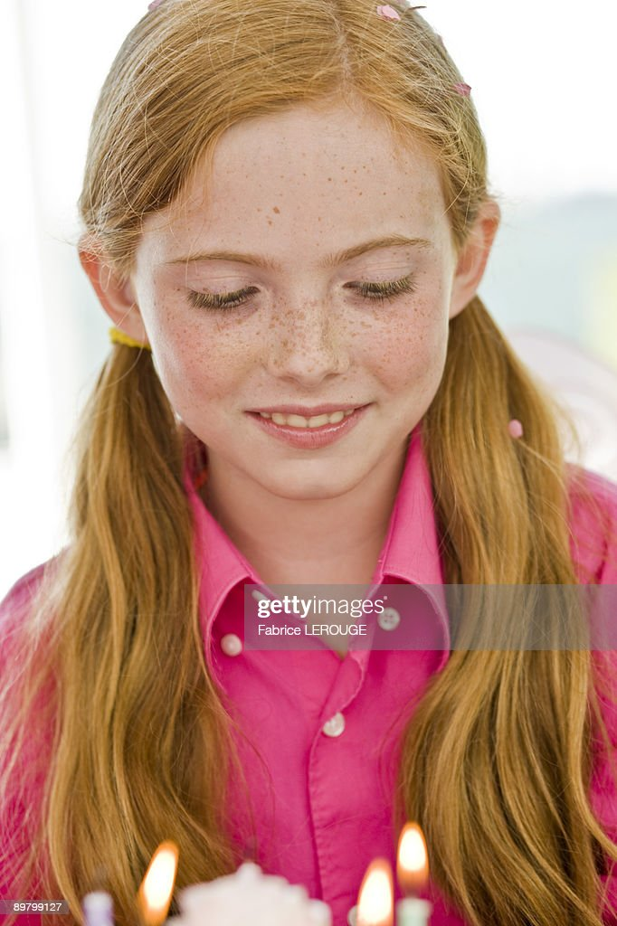 Close-up of a girl looking at a birthday cake : Stock Photo