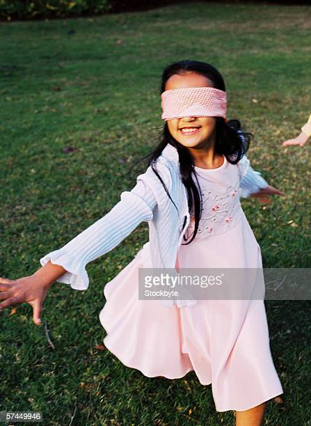 close-up of a girl (8-10) playing catch with a blindfold on