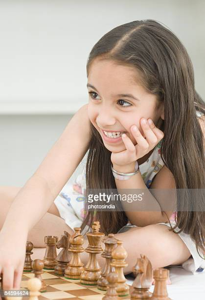 Close-up of a girl playing chess and smiling