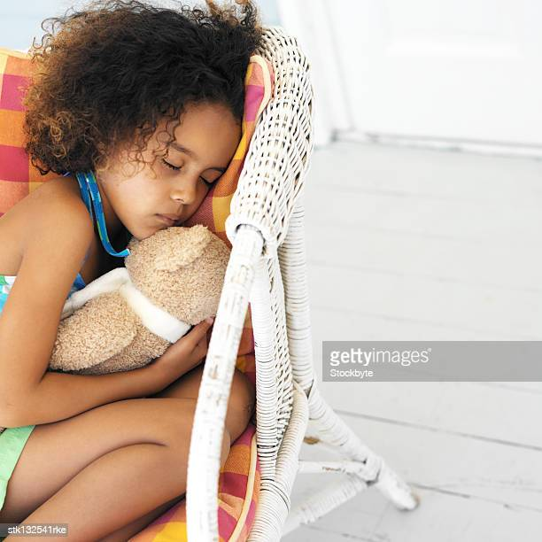 close-up of a girl sleeping with a teddy bear on a wicker chair