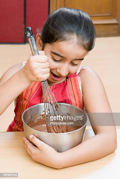 Close-up of a girl stirring chocolate sauce with an egg beater