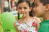 Close-up of a girl with a party horn blower in her mouth and her two friends beside her